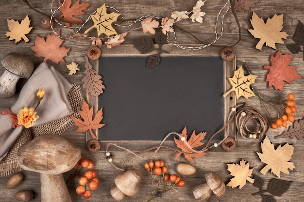 Pizarra enmarcada con decoraciones otoñales en espacio de madera