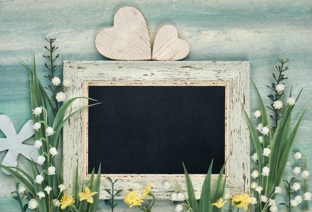 Pizarra enmarcada con flores de primavera en neutral, copyspace para su texto
