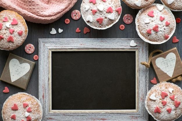 Pizarra enmarcada con magdalenas cubiertas de azúcar con corazones de glaseado de fondant rosa y blanco