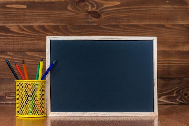 Una pizarra con espacio para texto, un juego de lápices de colores con un vaso sobre un fondo de madera