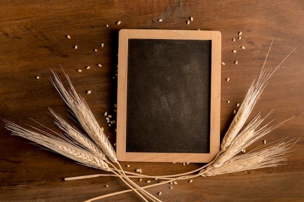 Pizarra y espiga de trigo en mesa de madera marrón