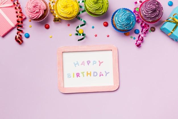 Pizarra de feliz cumpleaños con gemas de colores; serpentinas y muffins sobre fondo rosa