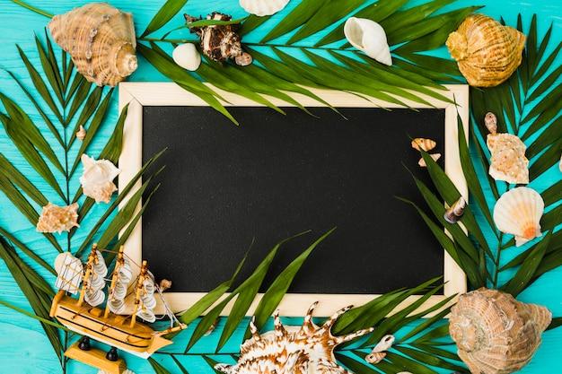 Pizarra y hojas de plantas con caracoles y barco de juguete.