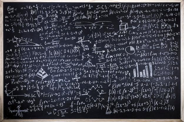 Pizarra inscrita con fórmulas científicas y cálculos en física y matemáticas