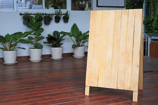 Pizarra de madera en blanco del menú en piso delante del restaurante.