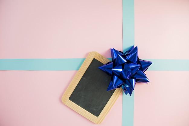Pizarra de madera sobre la caja de regalo atada con lazo y cinta.