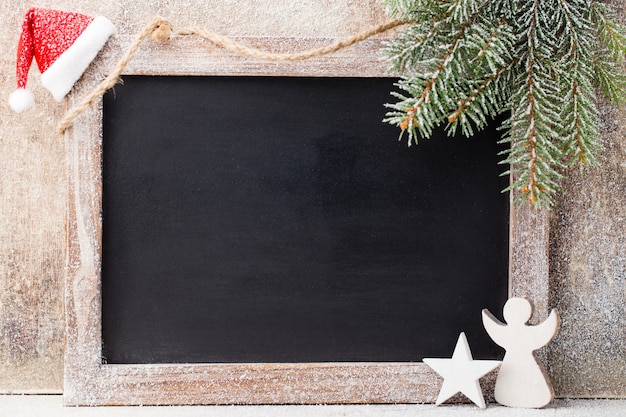 Pizarra de navidad con decoración. gorro de papá noel, estrellas, mesa de madera. estilo rústico vintage.
