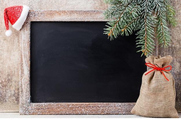 Pizarra de navidad y decoración sobre fondo de madera.