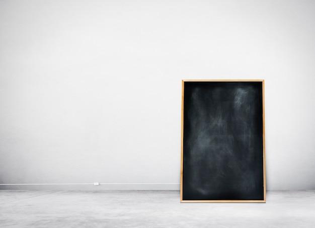 Pizarra negra en blanco sobre una pared blanca