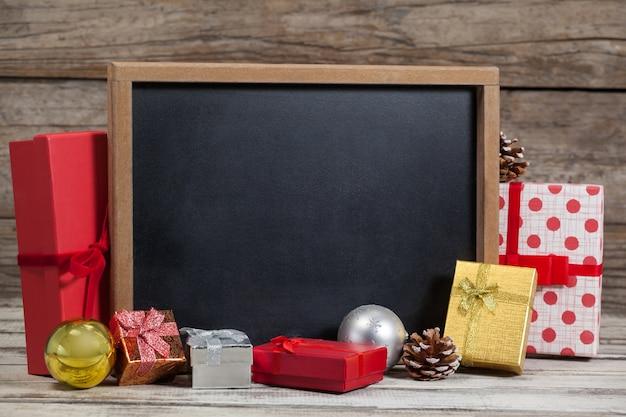 Pizarra negra con regalos alrededor