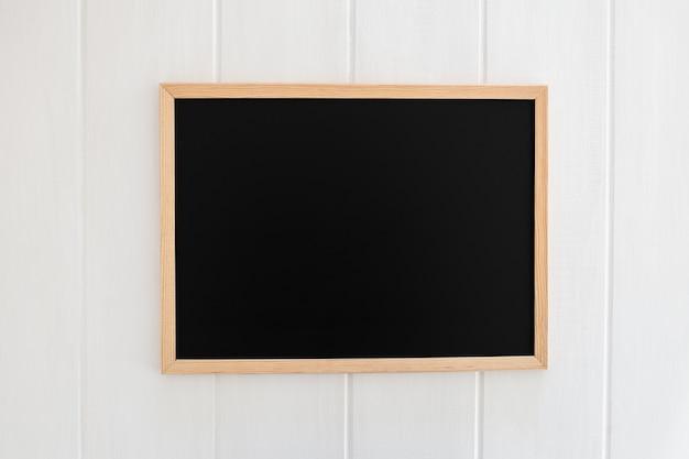 Pizarra negra sobre fondo blanco de madera