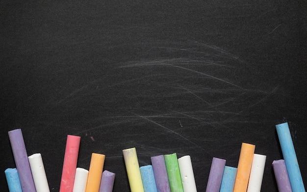 Pizarra negra vacía para el espacio de la copia con chalka colorido, ideal para la educación