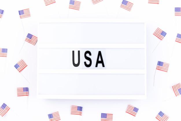 Pizarra con nota usa rodeada de pequeñas banderas americanas