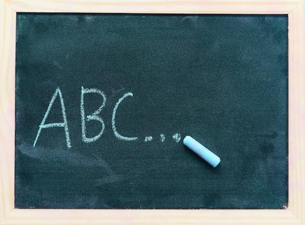 Pizarra oscura o pizarra con textura horizontal y pancarta / pizarra tiza dibujar y escribir abc para la educación en la pizarra de la escuela