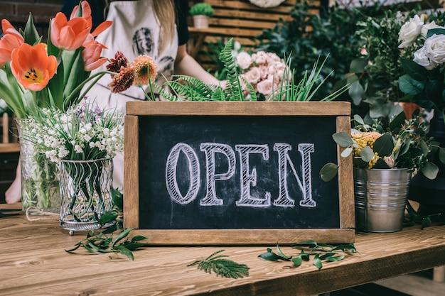 Pizarra con la palabra abierta en la tienda de flores