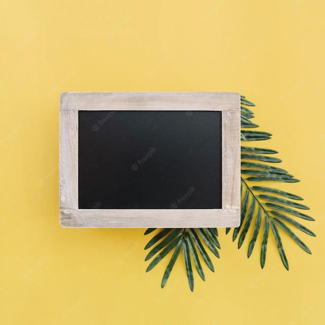 Pizarra para maqueta con hojas de palma sobre fondo amarillo