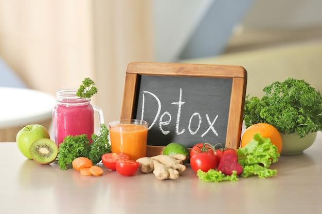 Pizarra pequeña con palabra detox, jugos e ingredientes frescos en la mesa