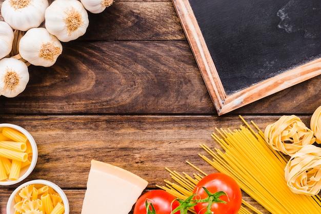 Pizarra y queso cerca de pasta y verduras