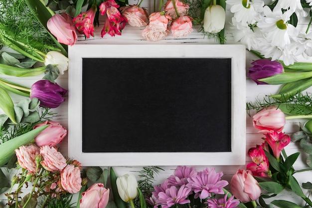 Pizarra rectangular en blanco rodeada de rosa; tulipán; flores de manzanilla y alstroemeria.