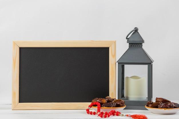 Pizarra rectangular pequeña con dátiles jugosos y candelero sobre fondo blanco