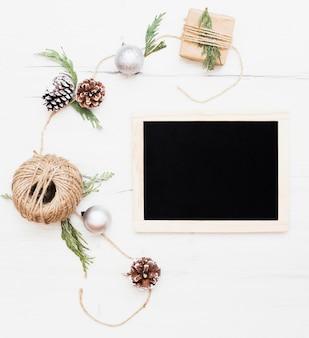 Pizarra rodeada de decoraciones navideñas de embalaje.