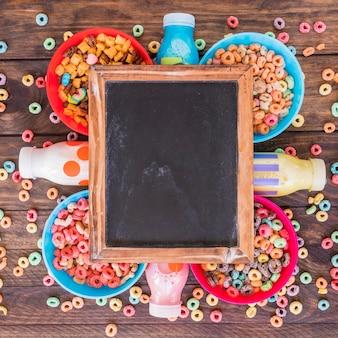 Pizarra sobre brillantes cuencos de cereales y botellas.