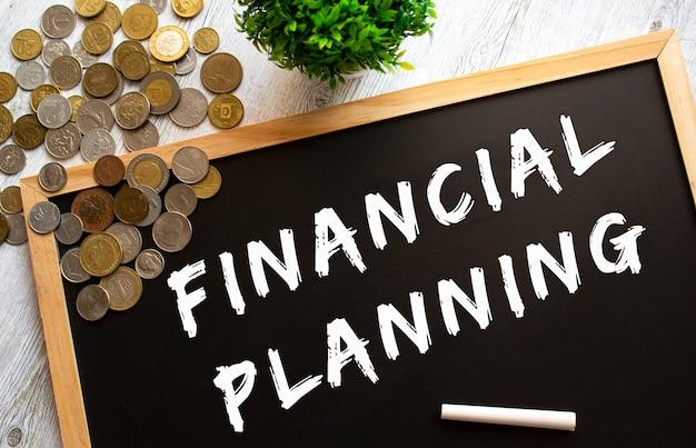 Pizarra con el texto planificación financiera y monedas de metal sobre una mesa de madera gris. concepto financiero.