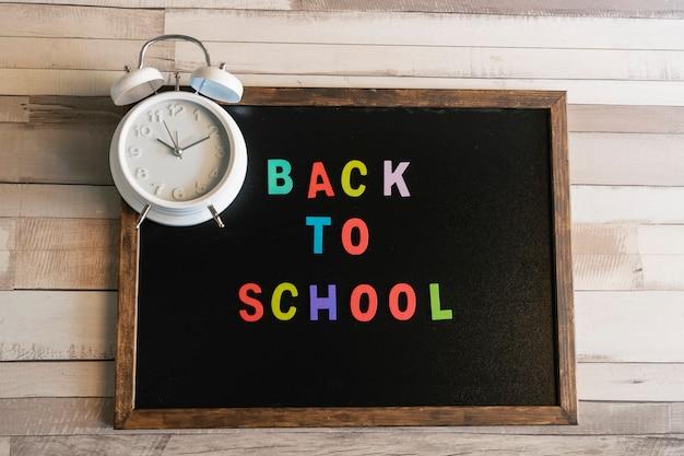 Pizarra con texto de regreso a la escuela y un reloj despertador