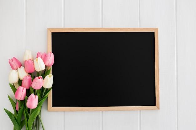 Pizarra con tulipanes sobre fondo blanco de madera