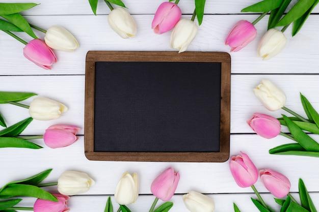 Pizarra vacía con una composición de primavera con tulipanes en madera blanca