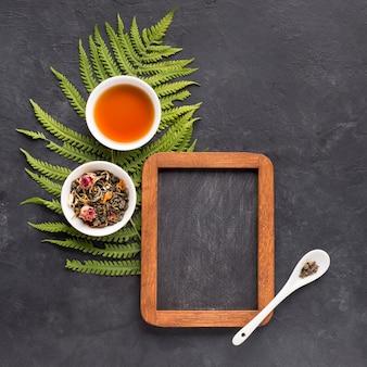 Pizarra vacía con hojas secas y té en un tazón de cerámica sobre fondo negro con textura