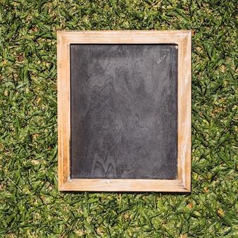 Pizarra vacía con marcos de madera sobre fondo verde