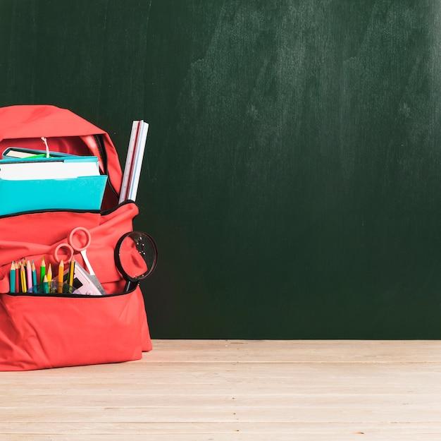 Pizarra vacía y mochila escolar roja con suministros