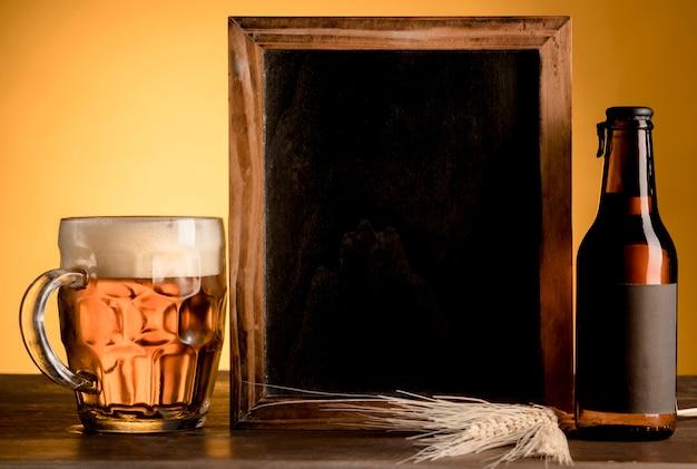 Pizarra y vaso de cerveza y botella alcohólica en mesa de madera