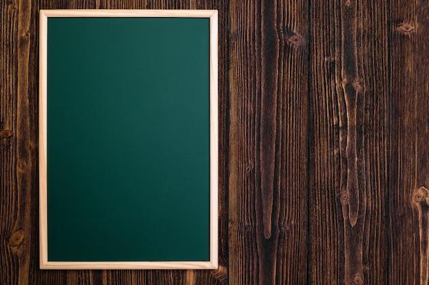 Pizarra verde vacía con marco de madera sobre madera