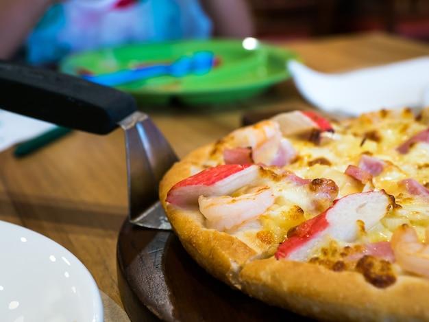 Pizca de mariscos pizza con cangrejo, camarones y jamón en una bandeja de madera.