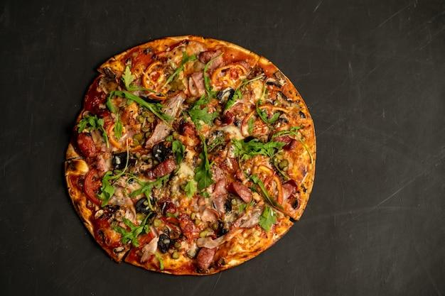Pizza apetitosa con salchichas ahumadas tocino carne tomate tomate rúcula en negro oscuro. con copyspace