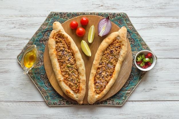 Pizza árabe lahmacun en mesa de madera blanca.