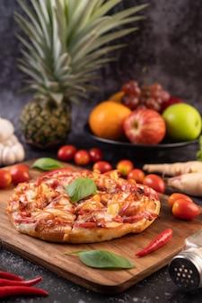 Pizza en bandeja de madera con tomate ají y albahaca.