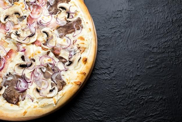 Pizza bbq sobre fondo negro, sobre una base de crema en combinación con mozzarella, bbq de ternera, tocino, champiñones, cebollas rojas en escabeche, delicious