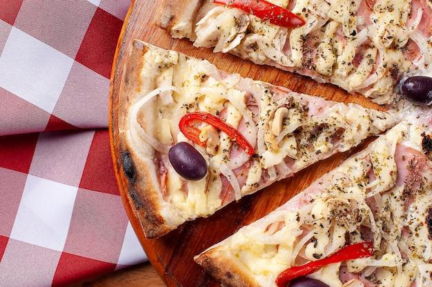 Pizza a la brasileña con queso mozzarella, cebolla, aceitunas, pechuga de pavo y pimiento rojo
