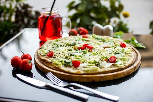 Pizza caezaron la tabla de madera lechuga parmesano tomate cherry galletas de pollo vista lateral