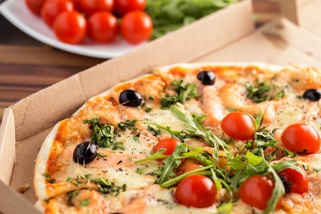 Pizza en caja de cartón sobre una mesa de cerca