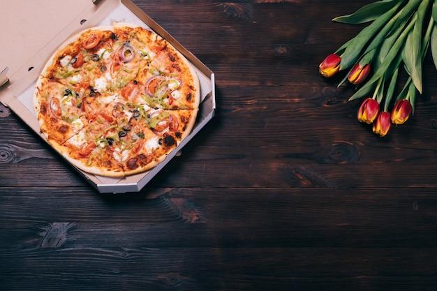 Pizza en una caja y un ramo de tulipanes