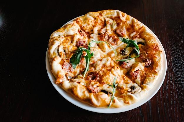 Pizza de carne italiana con rúcula en un escritorio de madera marrón