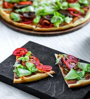 Pizza de carne con rodajas de tomate y pepino fresco