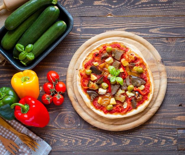 Pizza casera fresca con diferentes verduras sobre un fondo de madera