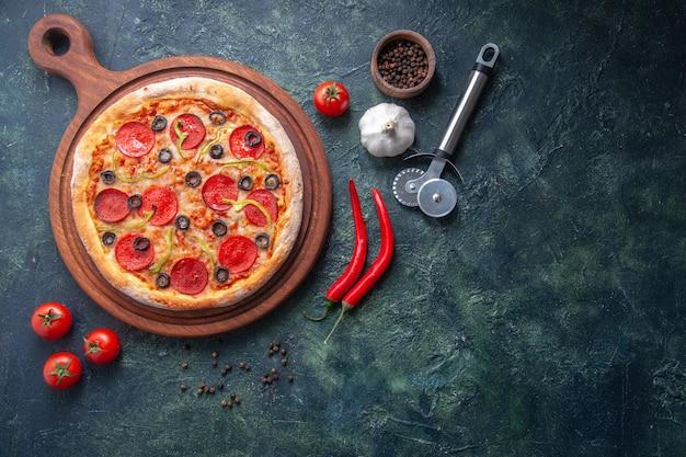 Pizza casera sobre tabla de cortar de madera y tomates pimiento ajo en superficie oscura aislada