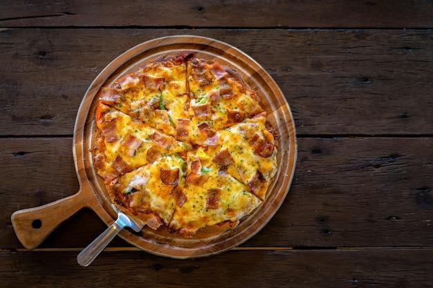 Pizza casera tradicional en restaurante en mesa de madera