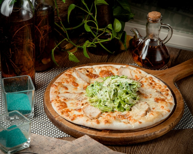 Pizza cesar con pollo, lechuga romana y parmesano rallado encima